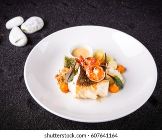 Main course in a restaurant with cod, marinated prawn, stir fried green cabbage and peanut crumbs on a white plate with a background of black sand