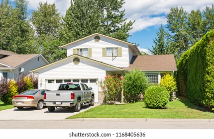 Main entrance of big residential house with car and truck parked on concrete driveway in front. Family house with landscaped front yard on blue sky background