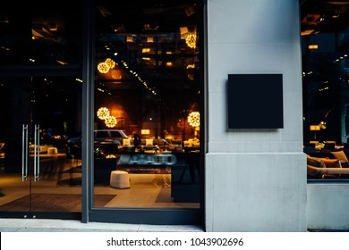 Main entrance of hotel, store or business company with mock up signboard with copy space area for your information Blank board of shop for add your design. City street with frontal door of store