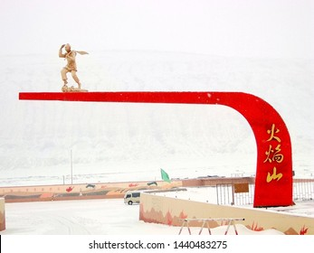 The main entrance of public Flaming Mountains with famous monkey statue in Turpan in Xinjiang in  China, part of Silk Road from China to Europe, covered by thick snow. 2012-12