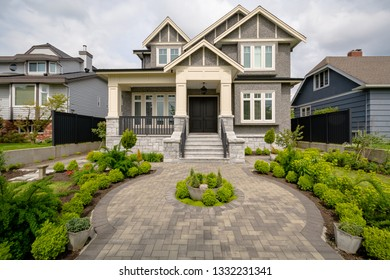 Main entrance of residential house with rounded paved pathway over front yard on cloudy day. Luxury residential house for sale