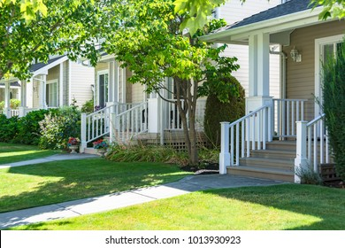 Main entrance of residential houses with lawn in front on bright sunny summer day