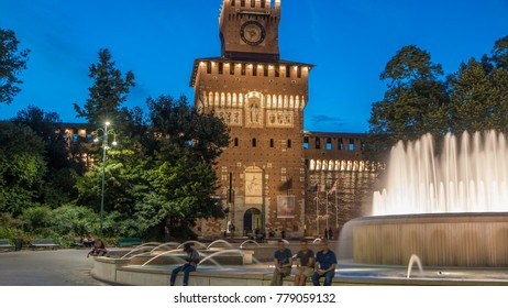 Main entrance to the Sforza Castle and tower - Castello Sforzesco illuminated day to nigh transition timelapse, Milan, Italy. Fountain and people walking around