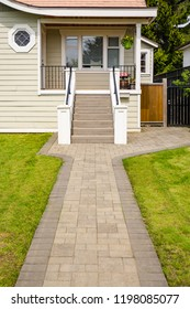 Main entrance of small residential house with paved walkway over green lawn of front yard. Family house with doorsteps to the entrance under the porch