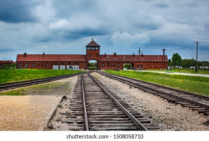Main gate to nazi concentration camp of Auschwitz Birkenau with train rail, Poland