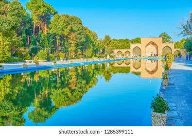 The main gates and the garden trees reflect on the water surface of the pool of Chehel Sotoun Palace in Isfahan, Iran