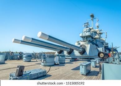 Main Gun on USS North Carolina Battleship under blue sky background.