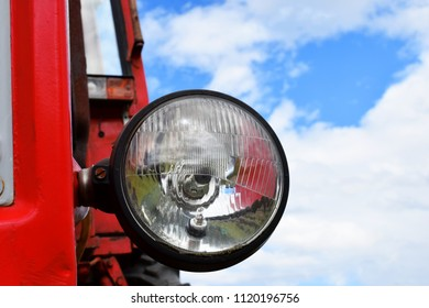 Main headlight of old red rusty tractor against cloudy sky background with copy space for text.