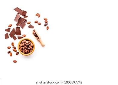 Main ingredient for chocolate. Cocoa beans near pieces of chocolate on white background top view copy space