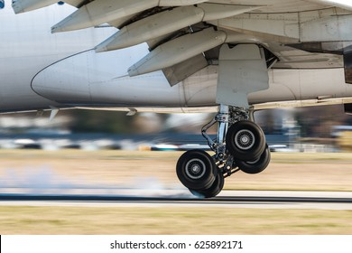 Main landing gear of big airplane during touchdown when wheel smoke