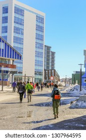 Main pedestrian street with modern building and walking people, Nuuk city center, Greenland
