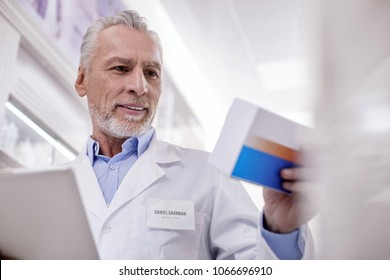 Main responsibility. Low angle of mature vigorous male pharmacist using tablet while scrutinizing medication