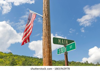 Main and South Street with American flag on utility pole with cloudy blue sky.
