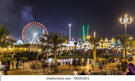 Main square and lake in Global Village with crowd and attractions timelapse in Dubai, UAE. Brightly colouredl lights and highly detailed pavilion facades have helped make Global Village one of Dubai's