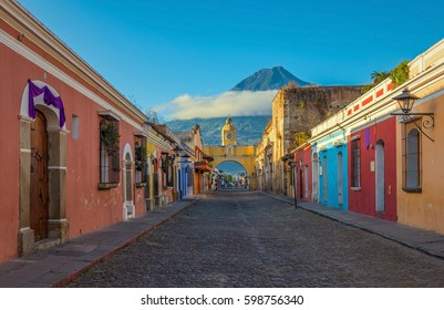 The main street of Antigua city with the yellow arch and the Agua volcano in the background during sunrise, Guatemala.