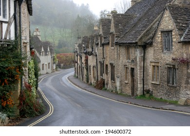The main street of Castle Combe village in Wiltshire  during winter showing ancient cottages and old world rooftops with Cotswold stone roof tiles and skylights