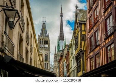 The main street Rue du Gros Horloge with the Rouen Cathedral tower and spires in view and half timbered homes along the way