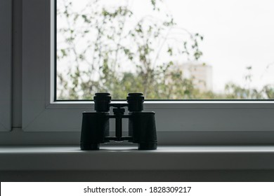 The main subject is out of focus, binoculars stand next to window voyeurism Mental Health Disorders spy on neighbors people concept