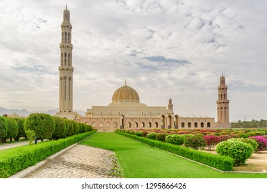 Main view of the Sultan Qaboos Grand Mosque and colorful gardens in Muscat, Oman. Amazing Islamic architecture. The Muslim place is a popular tourist attraction of the Middle East.