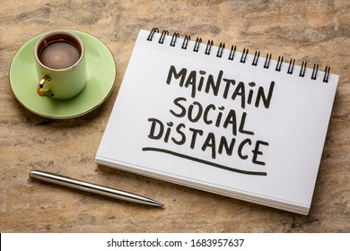 maintain social distance advice or reminder - handwriting in a spiral art sketchbook with a cup of coffee against handmade paper, infection control during covid-19 virus pandemic