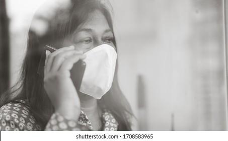 Erhaltung der psychischen Gesundheit von COVID-19 Coronavirus.Depression indische asiatische Frau mit Gesichtsmaske Handy zu Hause Panik und Angst vor finanziellen und psychischen Gesundheit.Arbeitslosigkeit finanzielle Not.