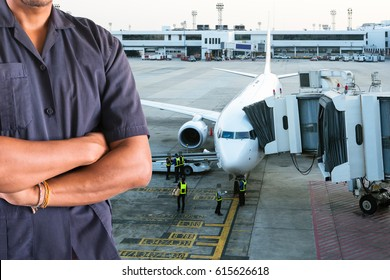 Maintenance engineer with an airplane at airport terminal gate preparing for next flight