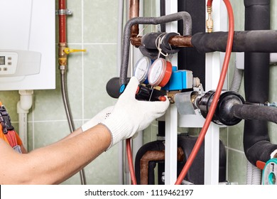 Maintenance engineer checking technical data of heating system equipment in a boiler room. Plumber installing pressure meter for house heating system.