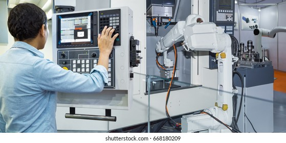 Maintenance engineer controlling industrial robotic holding automotive part with CNC machine in smart factory 4.0 concept
