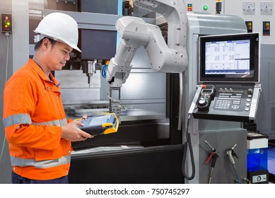 Maintenance engineer programming automatic robotic hand with CNC machine in smart factory. Industry 4.0 concept