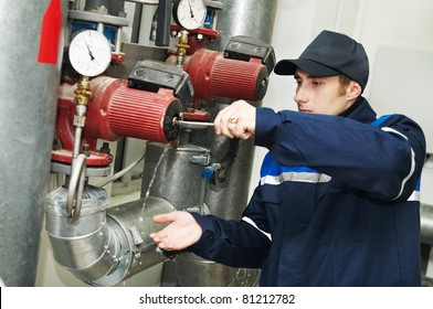maintenance engineer repairing water pump of heating system equipment in a boiler house