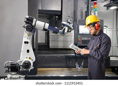 Maintenance engineer using digital tablet control automatic robotic hand with CNC machine in smart factory. Industry 4.0 concept