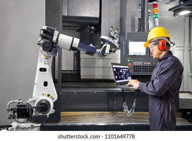 Maintenance engineer using laptop computer control automatic robotic hand with CNC machine in smart factory. Industry 4.0 concept