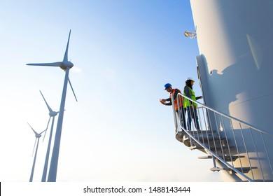 Maintenance engineers working on wind turbine in windfarm