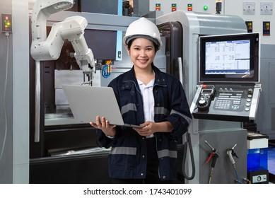 Wartung von Ingenieurinnen mit Laptop-Computersteuerung automatische Roboterhand mit CNC-Maschine in intelligenter Fabrik, Industrie 4.0-Konzept