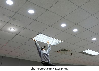 Maintenance man changing light bulbs in office