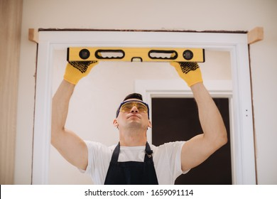 Maintenance man is fixing doors using a level measurement tool. He is wearing glasses, yellow gloves and a black apron