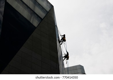 Maintenance Workers cleaning the exterior wall of the building secured by the ropes in Kuala Lumpur, Malaysia