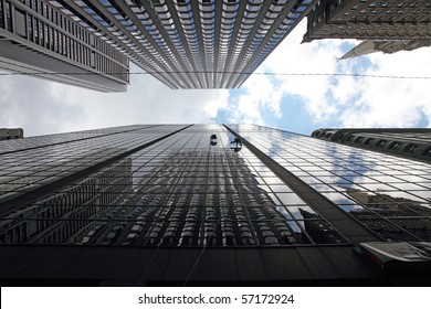Maintenance workers climbing outside a skyscraper and clean windows