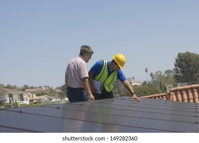 Maintenance workers inspecting solar panels on rooftop