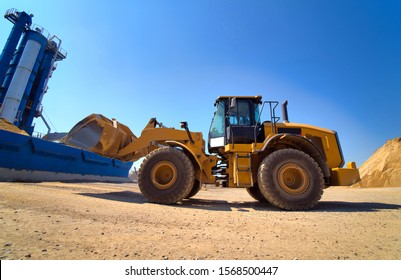 Maintenance of yellow excavator on a construction site against blue sky. wheel loader in sandheap background. Selective focus.