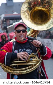 Mainz / Germany - February 15. 2020 European Guggen Music festival: Sousaphone player with his tuba, red cap and sunglasses while playing at the carnival parade