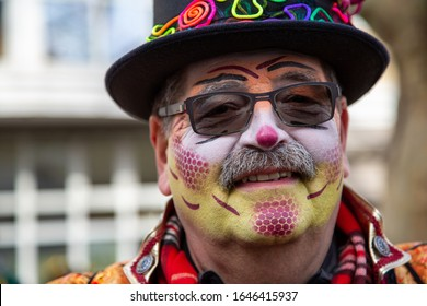 Mainz / Germany - February 15. 2020 European Guggen Music festival: Senior clown with beard, red nose hat and face paint at the carnival parade