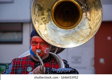 Mainz / Germany - February 15. 2020 European Guggen Music festival: Sousaphon player with his tuba and colored face at the carnival parade