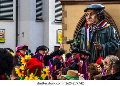 "MAINZ, GERMANY - FEBRUARY 27, 2017:  Unknown participants of the ""Rosenmontag parade"" on a parade float at the carnival in Mainz. The statue on the float shows Johannes Gutenberg."