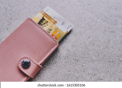 Mainz, Germany - January 14, 2020: banking cards and Mastercard looking out of pink RFID protection wallet against bright background, with copy space