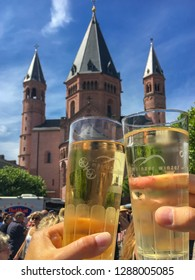 Mainz, Germany – July 29, 2017: Two clinking glasses with spritzer (Weinschorle) at Mainzer Marktfruehstueck in front of Mainz Cathedral in summer