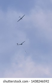 Mainz, Germany - June 20, 2019: Two gliders against cloudy sky, one is pulling up, the other is flying above, over small airfield in Mainz, Germany