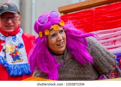 Mainz, Germany - March 04, 2019: portrait of a woman in flower power style with pink toupee and big sunglasses during the traditional carnival parade at shrove monday