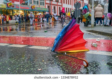 Mainz, Germany - March 04, 2019: broken colorful umbrella is lying on wet street during heavy storm and rain at carnival parade at shrove monday