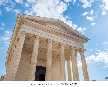 Maison Carree, mean square house in French, ancient Roman temple in Nimes, France, under cloudy blue sky